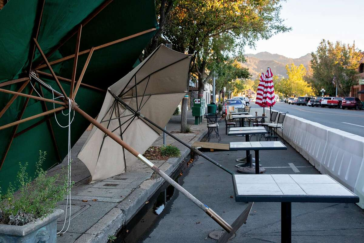 Umbrellas are seen knocked over by the wind outside Hydro Grill in Calistoga. Powerful winds are predicted to gust through the weekend, extending fire risk and threat of Bay Area blackouts.