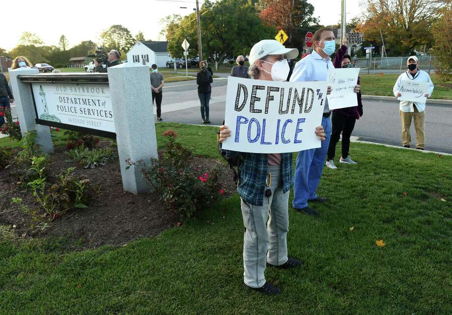 """Sue Huybensz, center, of Deep River and others gather outside Old Saybrook police headquarters to protest an incident involving the local officers and a resident with Down Syndrome. Mark Hand, a member of the Citizens' Police Review of Old Saybrook, which organized the event, said the group is concerned about """"the lack of transparency with the police commission and their oversight of the Department of Police Services."""" The group, which formed several months ago, organized the rally within 24 hours of the incident with the Roy family. """"Abuse of authority by the police department and the chief, as well, is just not something citizens want to sit by and watch and accept,"""" Hand said. """"We want to stress our pain and outrage and hope and demands for change,"""" he added. Roy had alleged in a Facebook post that police came to her family's cottage after receiving a report that a male driver had stolen a street sign. The officers """"aggressively"""" questioned her brother, Roy alleged, adding that she told the officers he could not be the person they were seeking as he is unable to drive.  Photo: Arnold Gold / Hearst Connecticut Media / New Haven Register"""