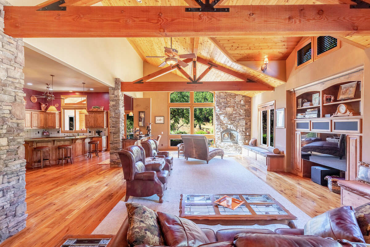 Inside the main house, vaulted ceilings, wood, stone and glass create an open living space.