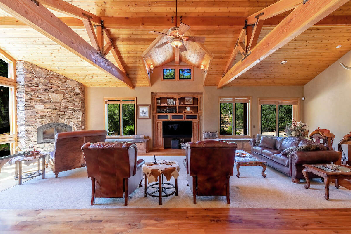 A stone hearth and open truss design soak the interior in warm light.