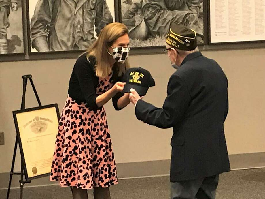 Lt. Gov. Susan Bysiewicz presents a cap that belonged to her late father to World War II veteran Raymond Tremblay. Photo: Jeff Mill / Hearst Connecticut Media