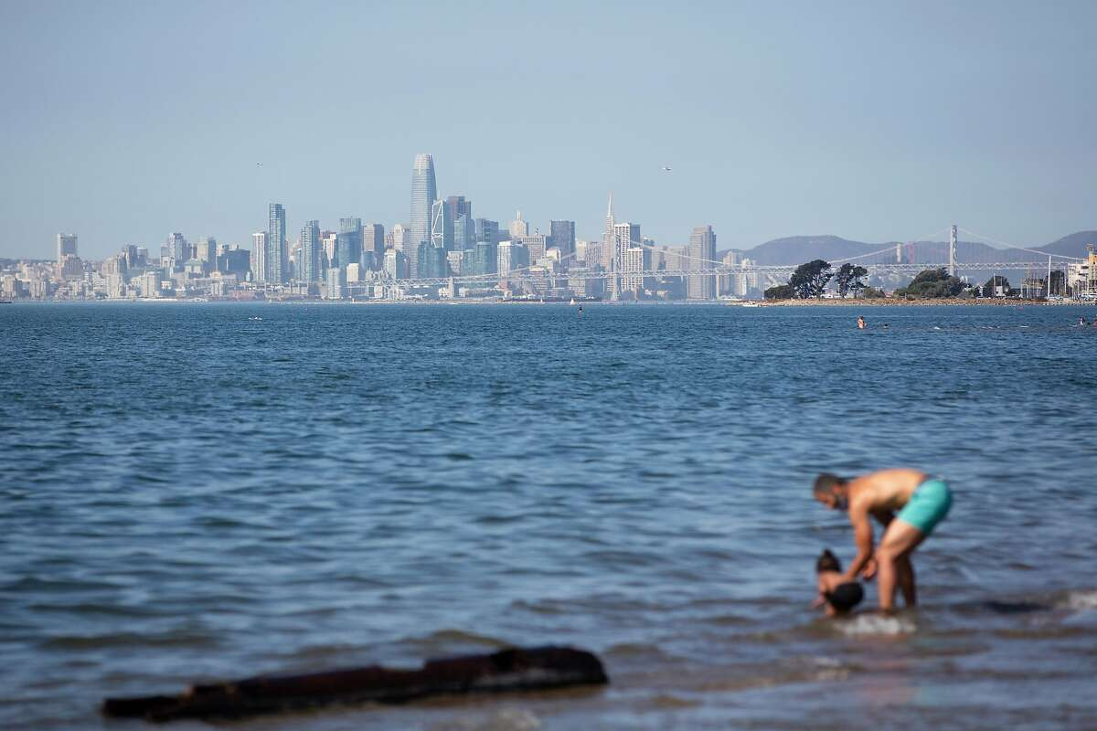 With the San Francisco skyline in the background, people play in the water at Crown Beach in Alameda during the heat wave.