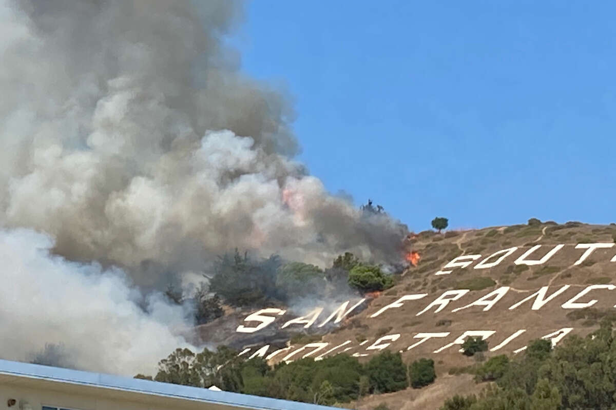 Firefighters are battling a four-alarm grass fire Friday afternoon on San Bruno Mountain in South San Francisco.