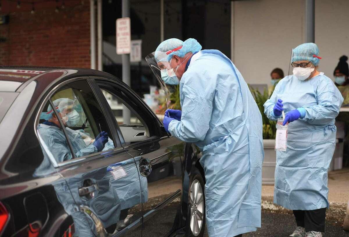 Dentist Tom McManus and dental hygienist Ana Dacosta administer a COVID-19 swab test outside the Community Health Center of Danbury on Delay Street in Danbury last week.