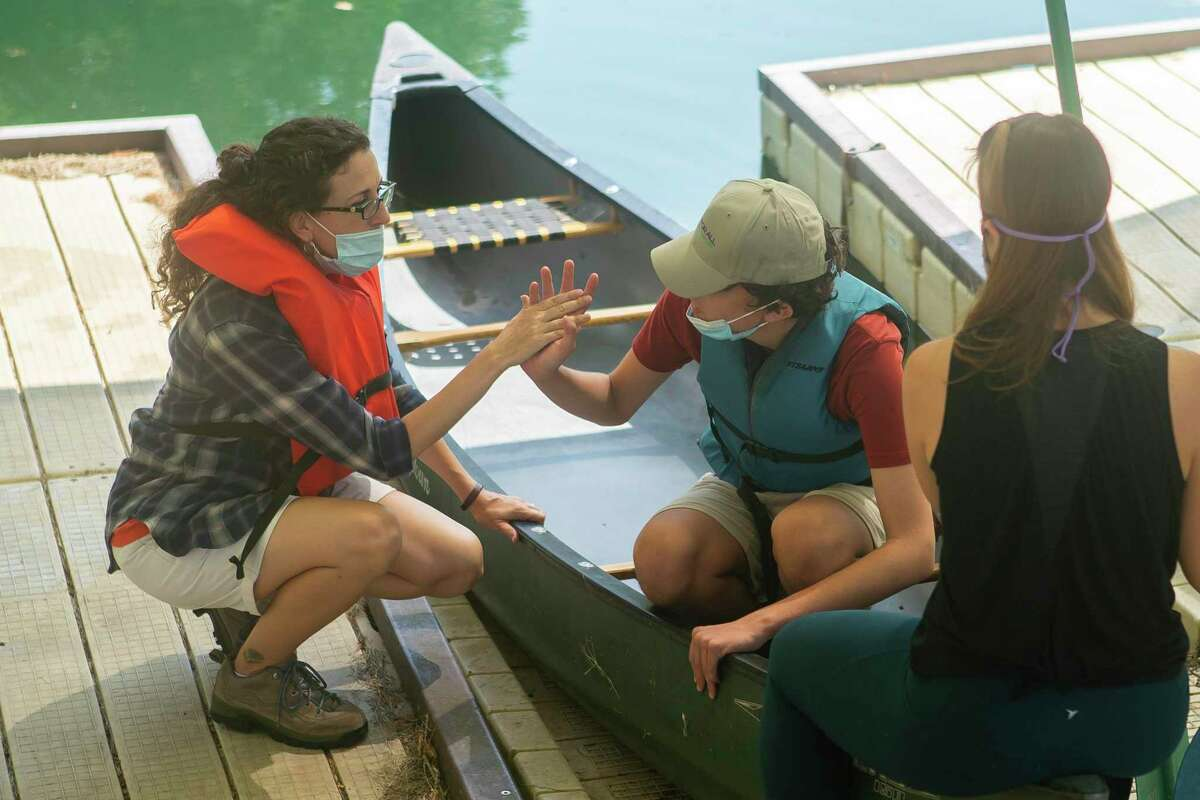 Suzanne Garofalo high-fives her son, Paul Perez, as they prepare to go canoeing at Camp For All, Saturday, Oct. 10, 2020, in Burton, TX.