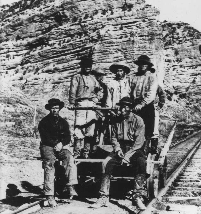 Seven men on railroad handcar. Shows men on handcar; they are Chinese, white, and African-American.
