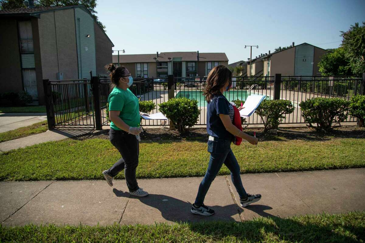 """Communities in Schools student support manager Nguyet """"Mimi"""" Tran and Bush Elementary School family liaison Johana Santacruz walk an apartment complex in Alief on Friday, Oct. 2, 2020, making visits to families of students who were either not enrolled or were not consistently attending class."""