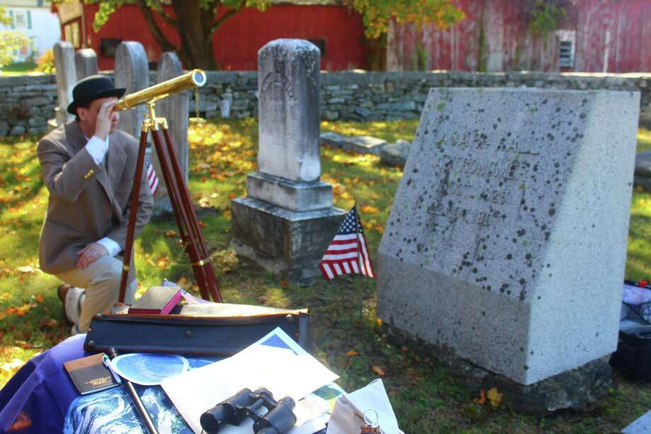 Historian and reenactor Kevin Titus dressed up as astronomer Asphus Hall and held a birthday celebration for him at his grave in Goshen Center Cemetery. Hall was the U.S. Astronomer under President Abraham Lincoln, and is credited with discovering the moons around Mars. Here, Michael Esposito takes a look through Hall's telescope, part of a display of items belonging to the late astronomer. Photo: Kevin Titus / Contributed Photo /