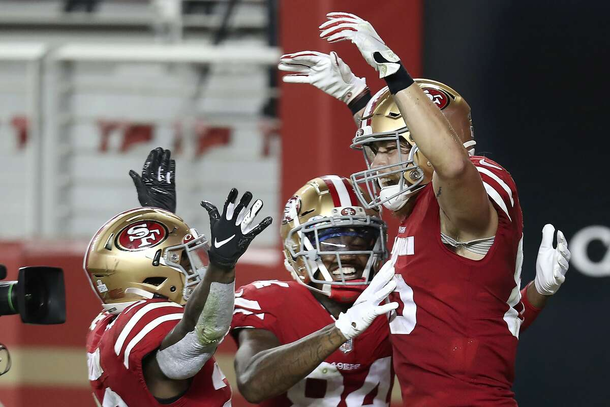 George Kittle (right) is congratulated by teammates after a touchdown reception against the Eagles on Oct. 4.
