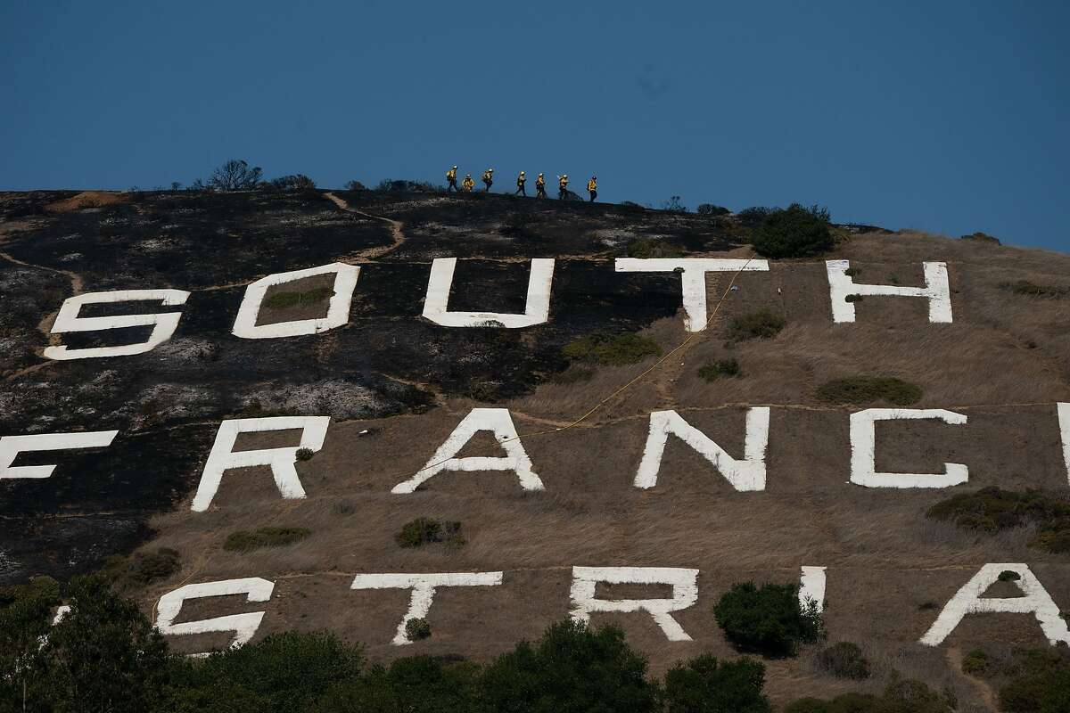 Firefighters are seen on the ridge above the South San Francisco sign Friday.