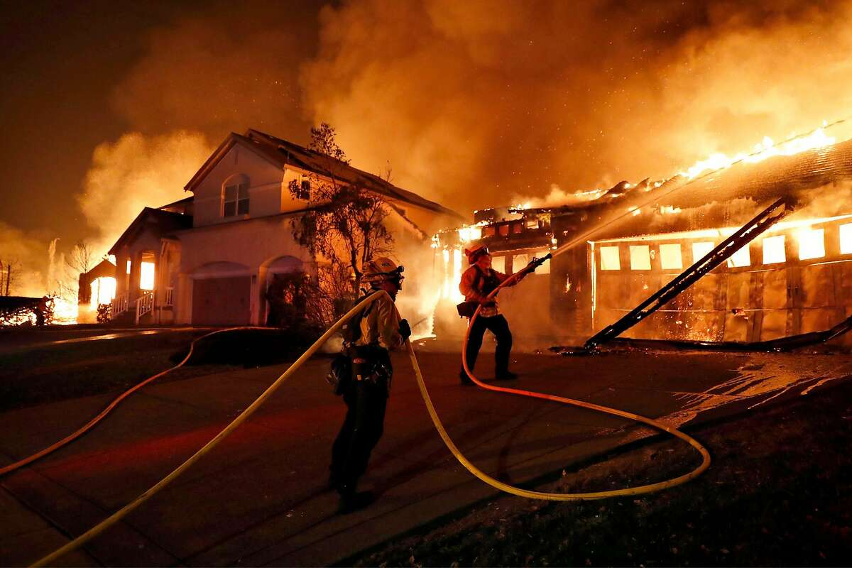 Firefighters try to keep house fires from spreading on Mountain Hawk Drive as the Shady Fire burns in the Skyhawk area of Santa Rosa in September.