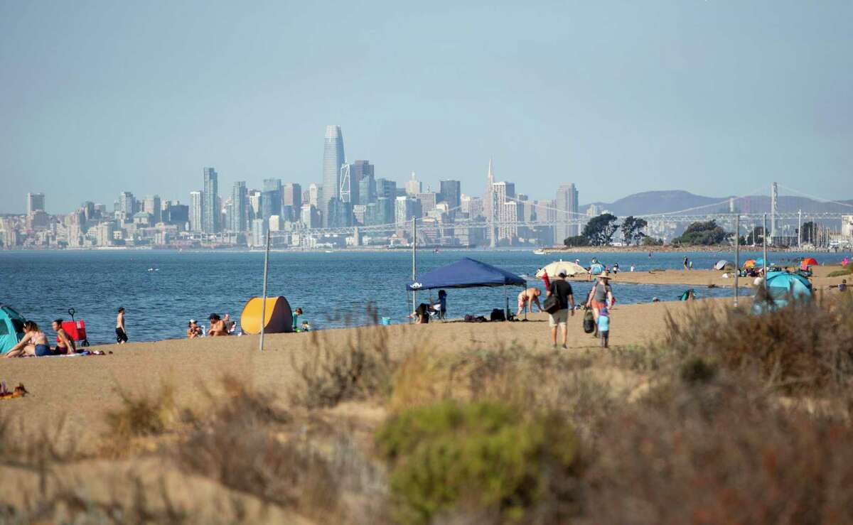 The San Francisco skyline is behind Alameda Beach as families play in the water and escape the heat on Friday, Oct. 16, 2020.