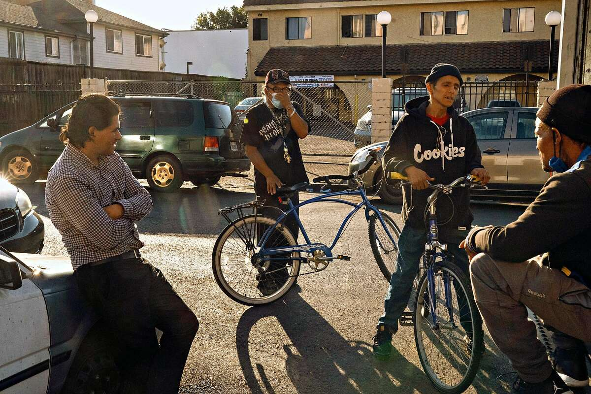 People gather near where a 39-year-old man was killed and two other people were wounded in a shooting Thursday night at the sidewalk here at the 1400 Bloc of 89th Ave.on Thursday, Oct. 16, 2020 in Oakland, Calif. The name of the man killed has not been released yet. Authorities said the two wounded were a 58-year-old woman and a 62-year-old man.