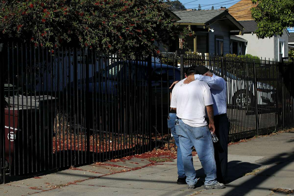 """Pastor Jose Rojas of the Pentecostals of Oakland, right, prays with a couple who lost a loved one during a fatal shooting in the 1900 block of 84th Ave. in Oakland, Calif., on Wednesday, October 14, 2020. Rojas identified the 19-year-old victim by his nickname Lalo. """"I know the mom and dad and family. He was one of our Sunday school kids,"""" Rojas said, who hasn't seen him for two years. """"I pray for this city everyday. Sometimes we wish we could do more."""" The event left three shooting victims, with two fatalities. This incident marks the 77th and 78th homicides of the year in Oakland."""