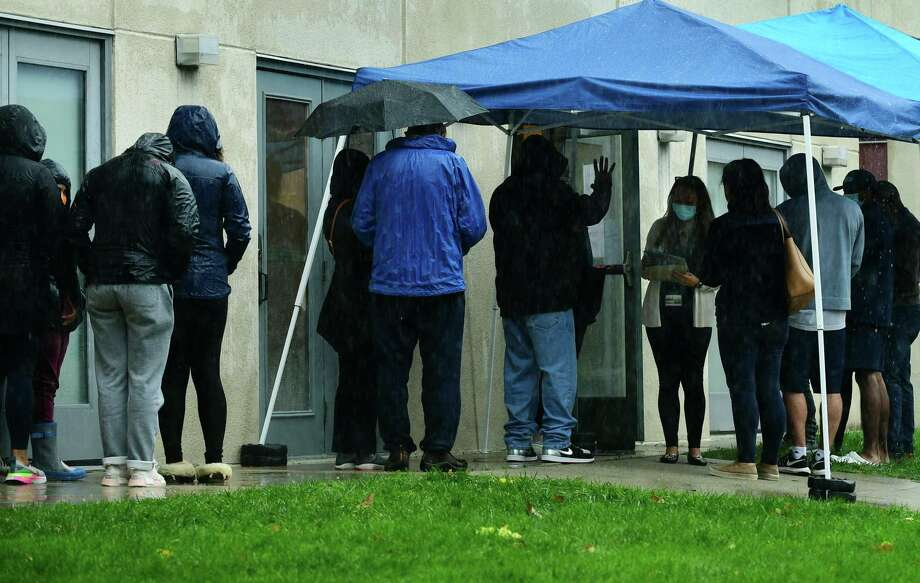 Staff at the Community Health Center on Day Street address the line of local residents waiting outside to get tested for the coronavirus Friday, October 16, 2020, in Norwalk, Conn. Photo: Erik Trautmann / Hearst Connecticut Media / Norwalk Hour