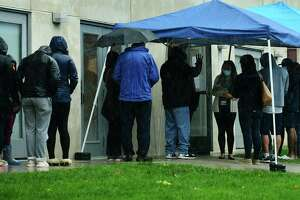 Staff at the Community Health Center on Day Street address the line of local residents waiting outside to get tested for the coronavirus Friday, October 16, 2020, in Norwalk, Conn.