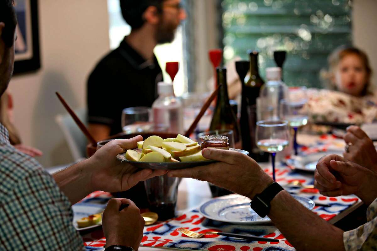(Left to right) Gabi Moskowitz's brother Jeremy Moskowitz passes a plate of apples and honey to their father Larry Moskowitz during dinner for Rosh Hashanah on Friday, September 18, 2020, in Novato, Calif. Gabi is celebrating with her family with a small dinner at home.
