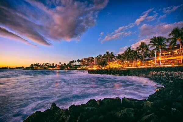 The sun sets along Alii Drive on the beach town of Kailua Kona on the Big Island of Hawaii.