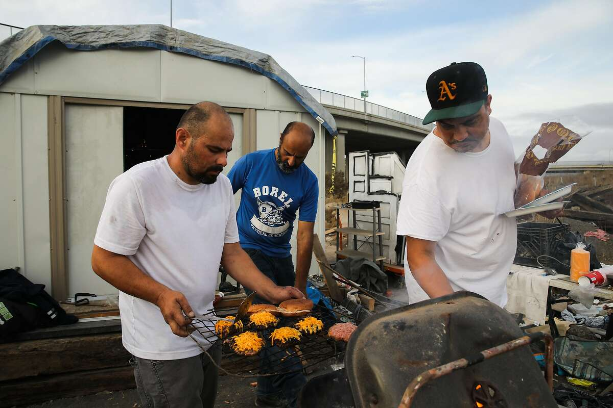 James Ayles, 37 (left), Moose Saberi, 44, and Gabriel Cano, 42, grill cheeseburgers at the Wood Street encampment in Oakland. Saberi has been unsheltered for four or five years.