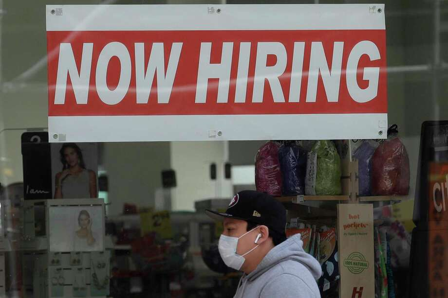 FILE - In this May 7, 2020, file photo, a man wearing a mask walks under a Now Hiring sign at a CVS Pharmacy during the coronavirus outbreak in San Francisco. California has regained more than a third of the 2.6 million nonfarm jobs the most populous state lost to the coronavirus pandemic in March and April. State officials reported Friday, Oct. 16, 2020, that the leisure and hospitality sector accounted for half the overall gain of 96,000 jobs as restaurants, hotels and other hospitality businesses benefitted from the state's easing of restrictions designed to slow the virus' spread. (AP Photo/Jeff Chiu, File) Photo: Jeff Chiu, STF / Associated Press / Copyright 2020 The Associated Press. All rights reserved
