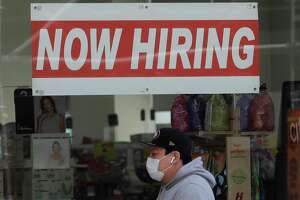 FILE - In this May 7, 2020, file photo, a man wearing a mask walks under a Now Hiring sign at a CVS Pharmacy during the coronavirus outbreak in San Francisco. California has regained more than a third of the 2.6 million nonfarm jobs the most populous state lost to the coronavirus pandemic in March and April. State officials reported Friday, Oct. 16, 2020, that the leisure and hospitality sector accounted for half the overall gain of 96,000 jobs as restaurants, hotels and other hospitality businesses benefitted from the state's easing of restrictions designed to slow the virus' spread. (AP Photo/Jeff Chiu, File)