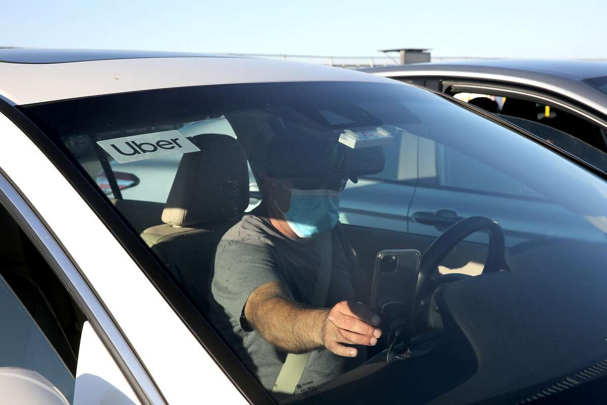 Uber driver Omer Iltas prepares to pick up a customer at S.F. International Airport in August. Proposition. 22 would classify drivers as independent contractors.