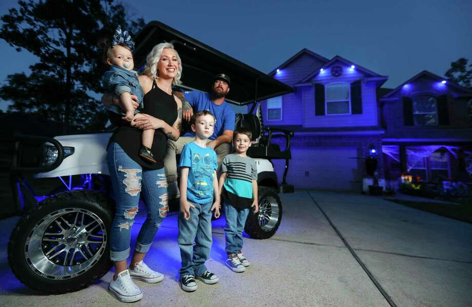 Brittany Stringfellow and her husband, Mike, poses for a portrait along their three children, Evie, 1, Jace, 6, and Benny, 5, in front of their blue-light house Wednesday in Conroe. Photo: Jason Fochtman, Houston Chronicle / Staff Photographer / 2020 © Houston Chronicle