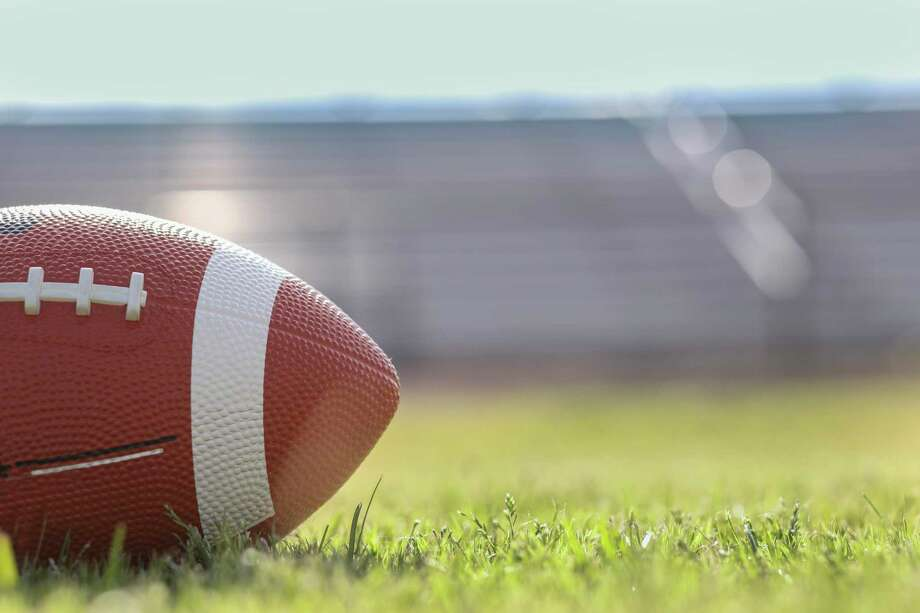Football on grass stadium on college or high school campus. Bleachers background. No people. Daytime. Photo: Fstop123 / Getty Images/iStockphoto / ©2019 FSTOP123