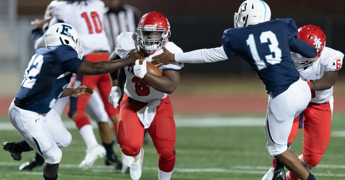 Jourdan Concepcion (8) of the Alief Taylor Lions runs up the middle in the first half between Joshua Pettos (32) and Jospeh McCaskill (13) of the Alief Elsik Rams during a High School football game on Friday, October 16, 2020 at Crump Stadium in Houston Texas.