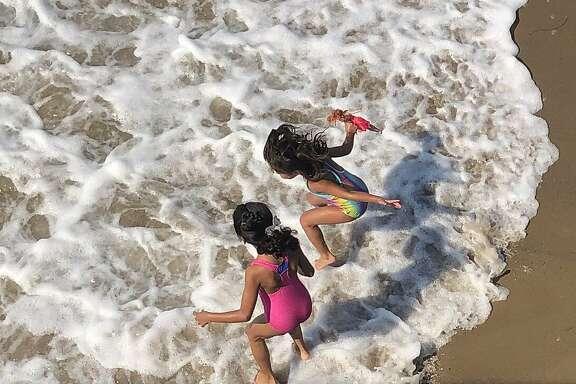Kids in surf and pier and boardwalk Ventura state beach