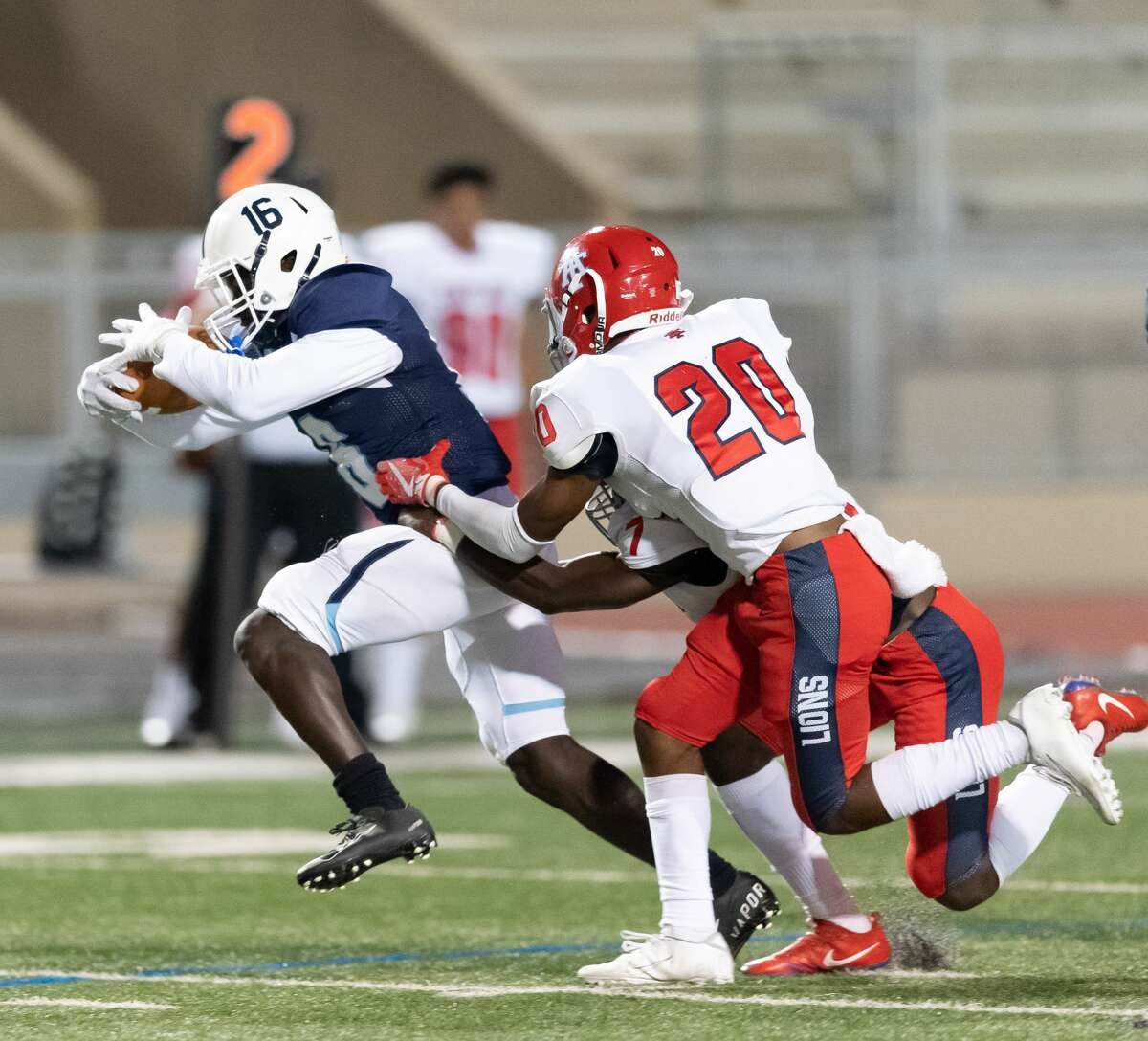 Joseph Nathaniel (16) of the Alief Elsik Rams is bright down in the first half after a short gain by Ekemini Ekwere (7) and Justin Jones (20) of the Alief Taylor Lions during a High School football game on Friday, October 16, 2020 at Crump Stadium in Houston Texas.