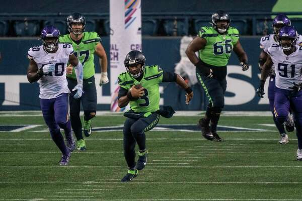 Seattle Seahawks quarterback Russell Wilson runs with the ball during the second half of the game against the Minnesota Vikings, on Sunday, Oct. 11, 2020, in Seattle. The Seahawks won 27-26. An average of 15.6 million viewers watched the game on NBC's Sunday Night Football.