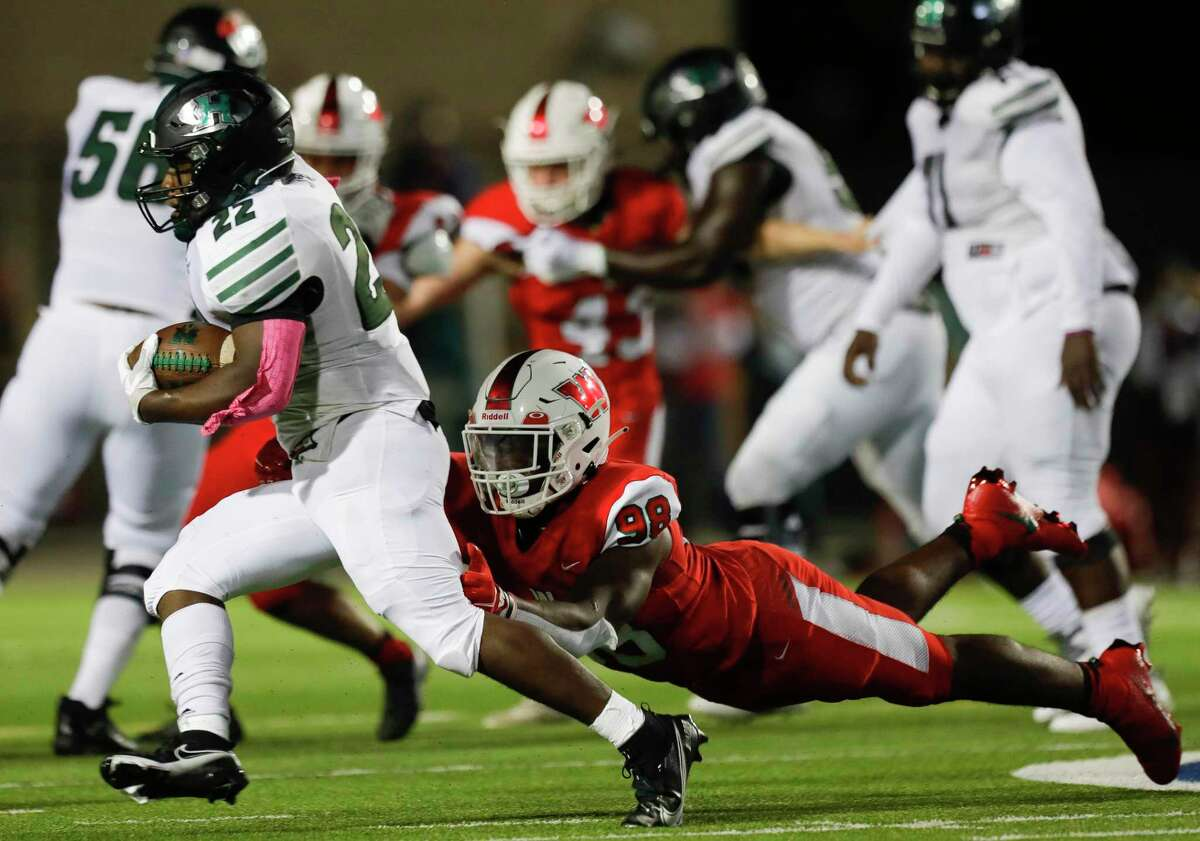 Fort Bend Hightower running back Charles Shelling (22) runs past a diving The Woodlands defensive linemen Bradley Warren (98) during the second quarter of a non-district high school football game at Woodforest Bank Stadium, Friday, Oct. 156 2020, in Shenandoah.