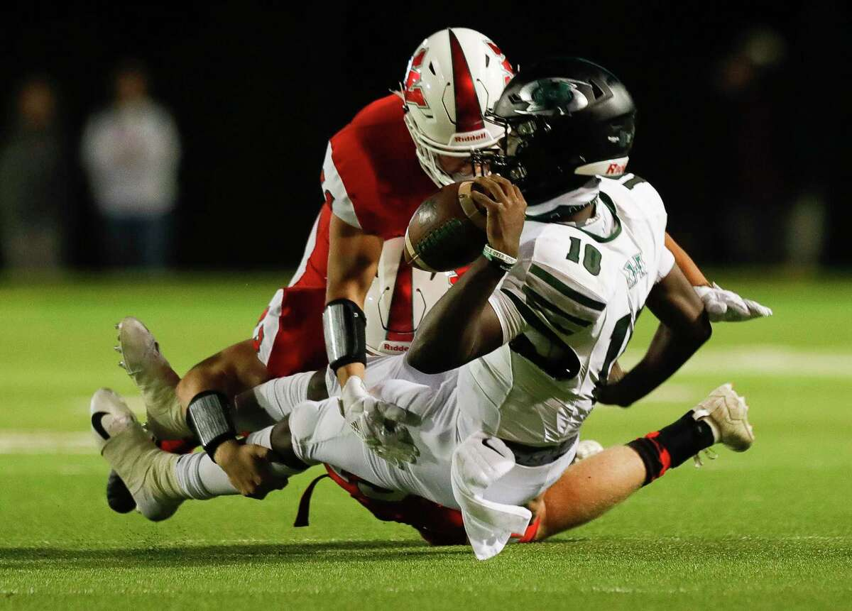 Fort Bend Hightower quarterback Jakolby Longino (10) is taken down by The Woodlands linebackers Matthew Knipfel (43) and Pablo Amaya (11) during the second quarter of a non-district high school football game at Woodforest Bank Stadium, Friday, Oct. 156 2020, in Shenandoah.