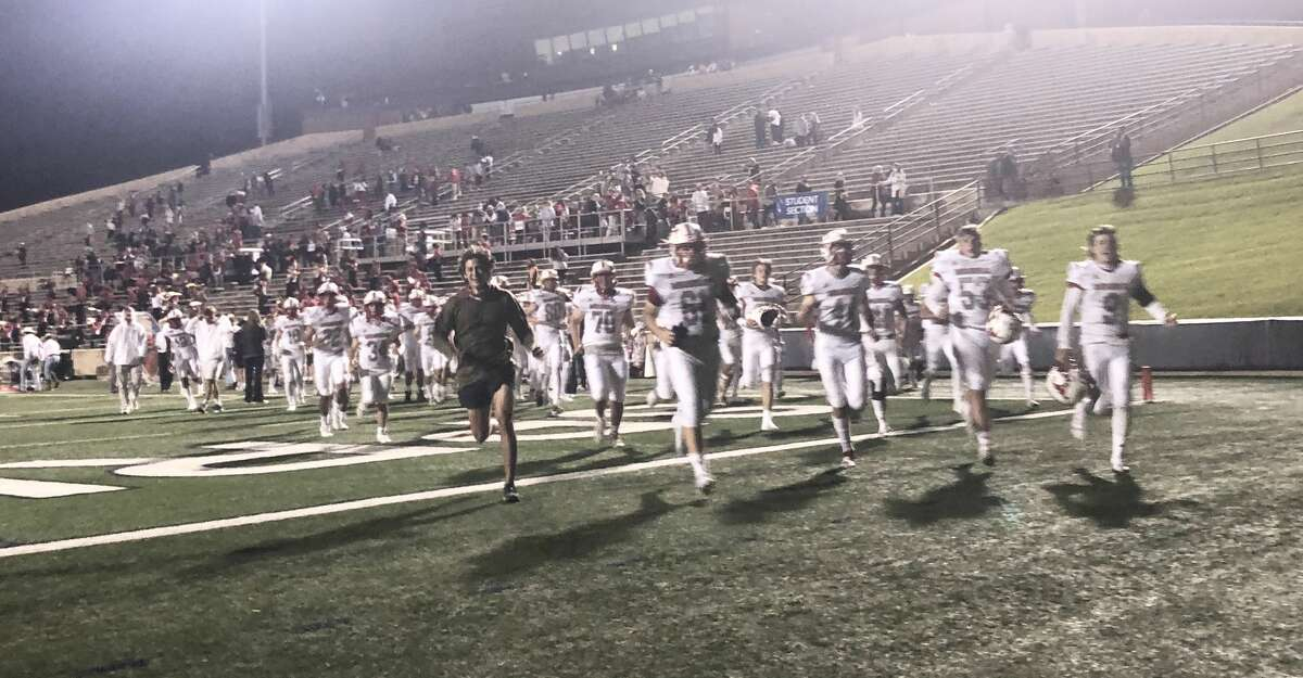 The Memorial Mustangs run off the field at Tully Stadium following their 41-0 victory over the Spring Woods Tigers on Oct. 16.