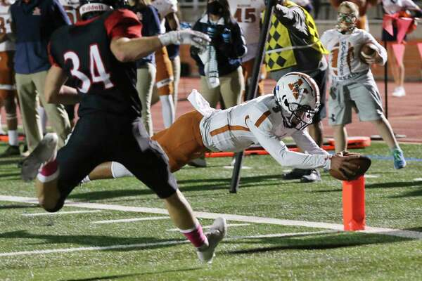 Madison quarterback Royal Kyle (03) dives in for his second touchdown in the first half against Churchill's Jack Tillman (34) during their football game at Heroes Stadium on Friday, Oct. 16, 2020.