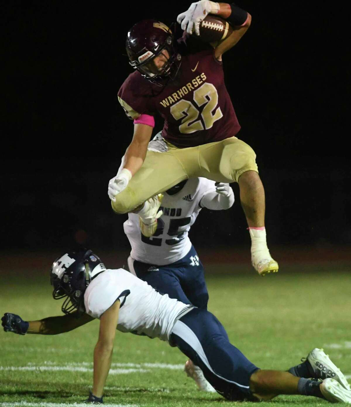 Devine running back Justin Contreras leaves one Hondo defender behind and hurdles another.