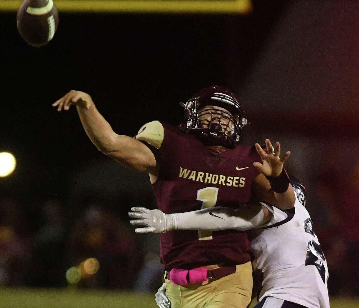 Hondo's Wyatt Bass hits Devine quarterback Brady Hackebeil in the Owls' win Friday night.