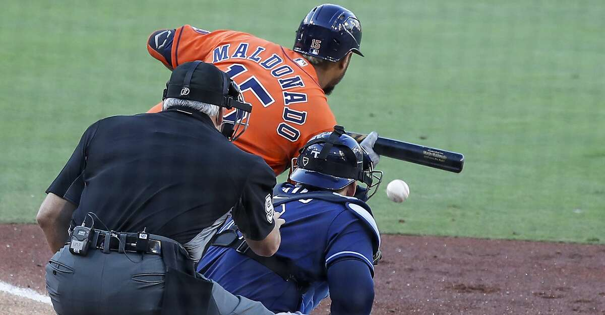 Houston Astros Martin Maldonado (15) lays down a sacrifice bunt in front of Tampa Bay Rays catcher Mike Zunino, moving Yuli Gurriel to 3rd and Aledmys Diaz to 2nd, during of Game 6 of the American League Championship Series at Petco Park Friday, Oct. 16, 2020, in San Diego.
