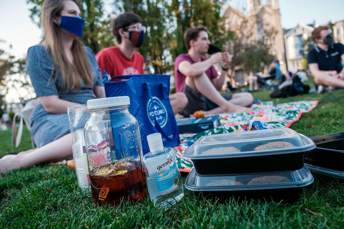 Cookies in take out containers, iced tea and plastic cups and hand sanitizer are seen at a gathering of friends in Washington Square in San Francisco on Friday, October 16, 2020. California is now allowing for small private gatherings of up to three pods for less than two hours.