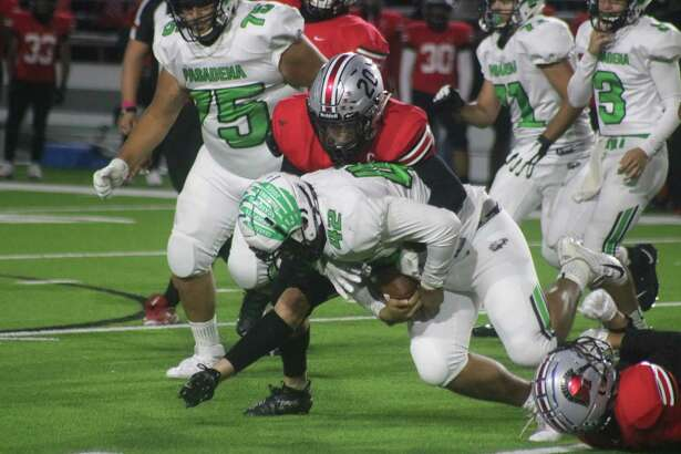 South Houston's Fidel Vizcaino wraps up Pasadena's Michael Lomas for little gain during the 63rd annual game Friday night.