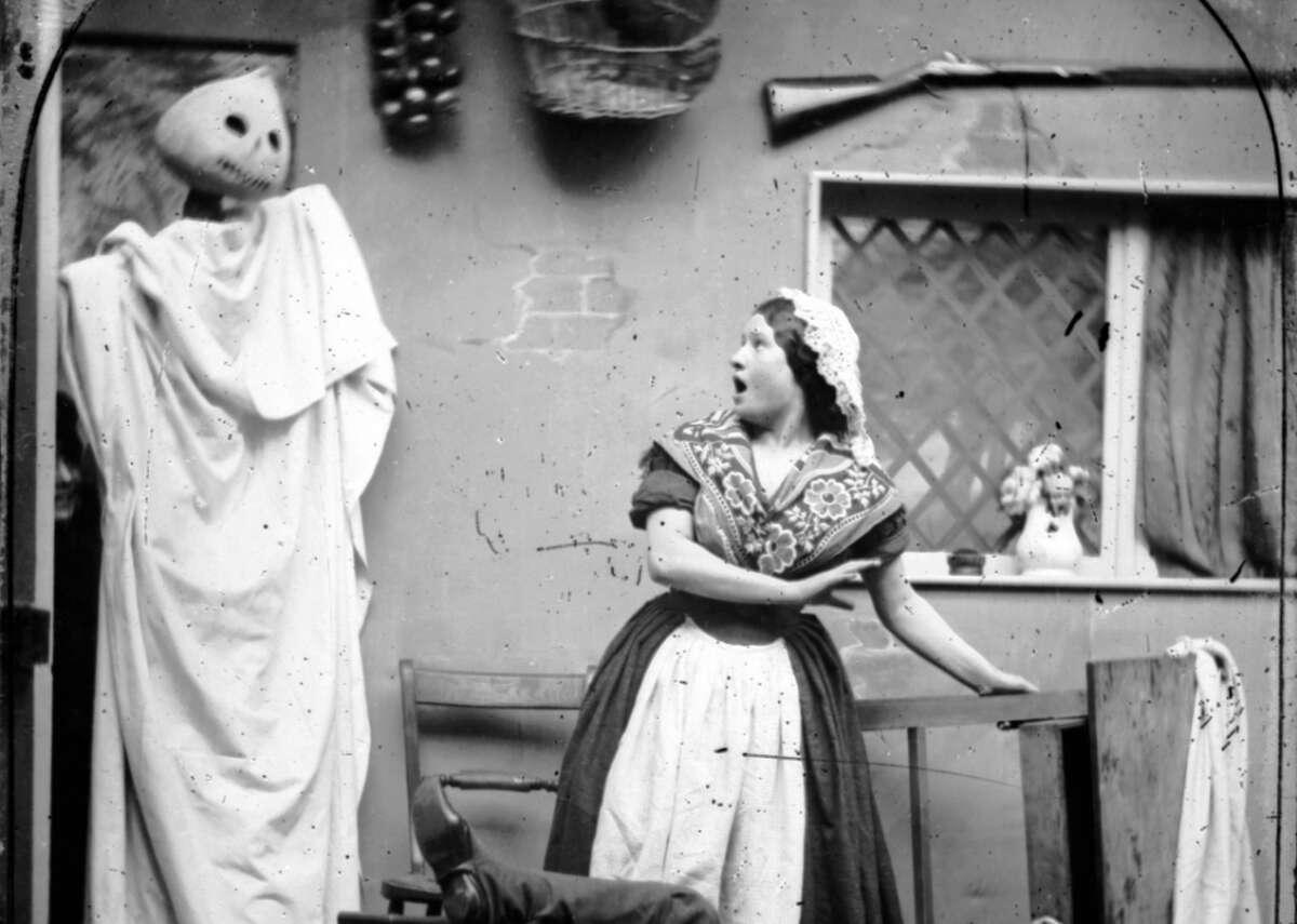 Halloween pumpkin mask A figure wearing a white cape and a Halloween pumpkin mask takes a person by surprise in their kitchen, circa 1865.
