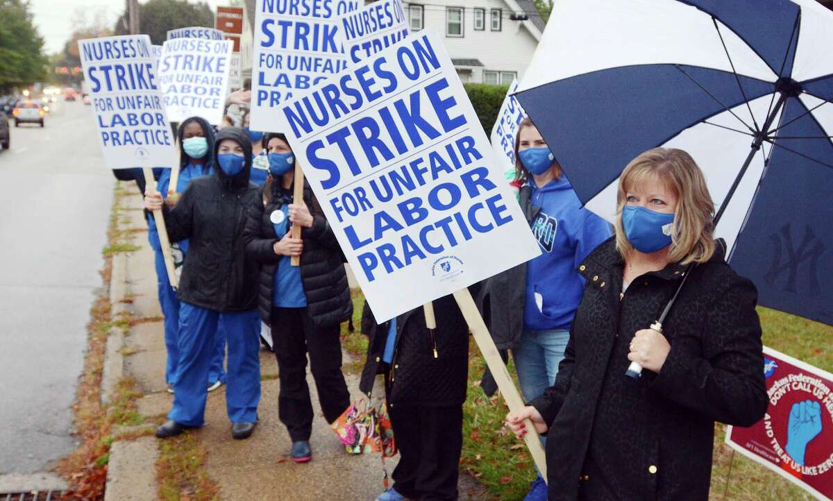 Registered nurse Julie Prochorena, right, of Colchester, Conn., joins a group of about 200 nurses and their supporters as they began a two-day strike outside the William W. Backus Hospital in Norwich, Conn., Tuesday, Oct. 13, 2020. The strike comes amid a breakdown in contract talks between the nurses' union and hospital management, as well as rising coronavirus cases in Norwich and other eastern Connecticut communities. The hospital is operated by Hartford HealthCare. (John Shishmanian/The Bulletin via AP)