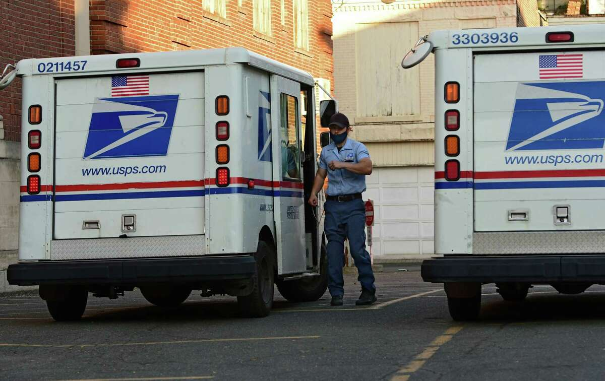A United State Postal Service mail carrier gets out of his truck behind the United States Post Office on Wednesday, Oct. 14, 2020 in Troy, N.Y. (Lori Van Buren/Times Union)