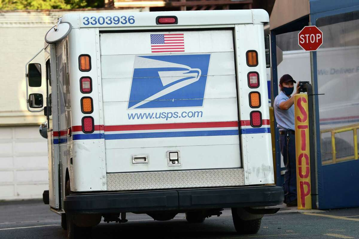 A United State Postal Service mail carrier gets out of his truck behind the United States Post Office and enters the building on Wednesday, Oct. 14, 2020 in Troy, N.Y. (Lori Van Buren/Times Union)
