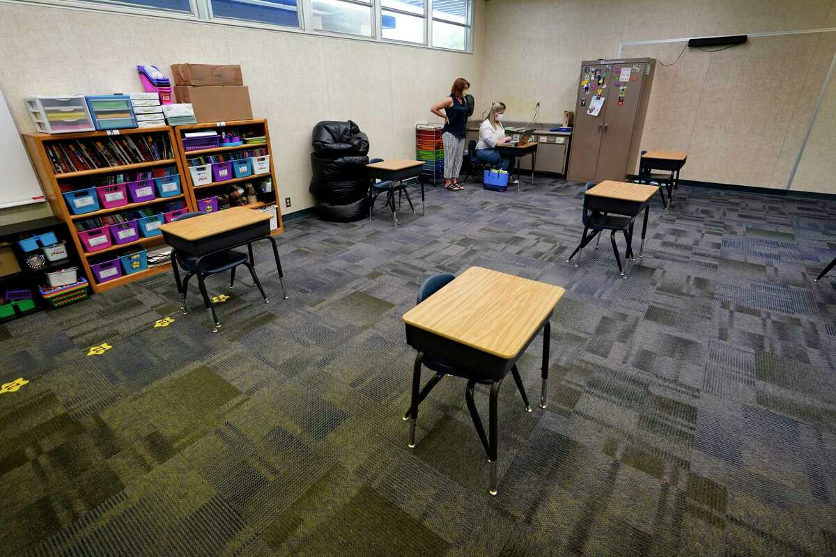 FILE - In this Aug. 19, 2020 file photo, teachers Andrea Gordon, left, and Melissa Stacy go over plans for classroom learning, among socially-distanced desks at Palm Vista Elementary School in Twentynine Palms, Calif. California has not seen a link between the reopening of K-12 schools for in-person learning and increased coronavirus transmission.