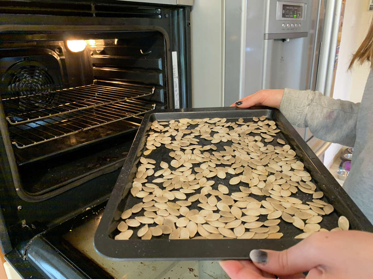 A baking tray with pumpkin seeds.