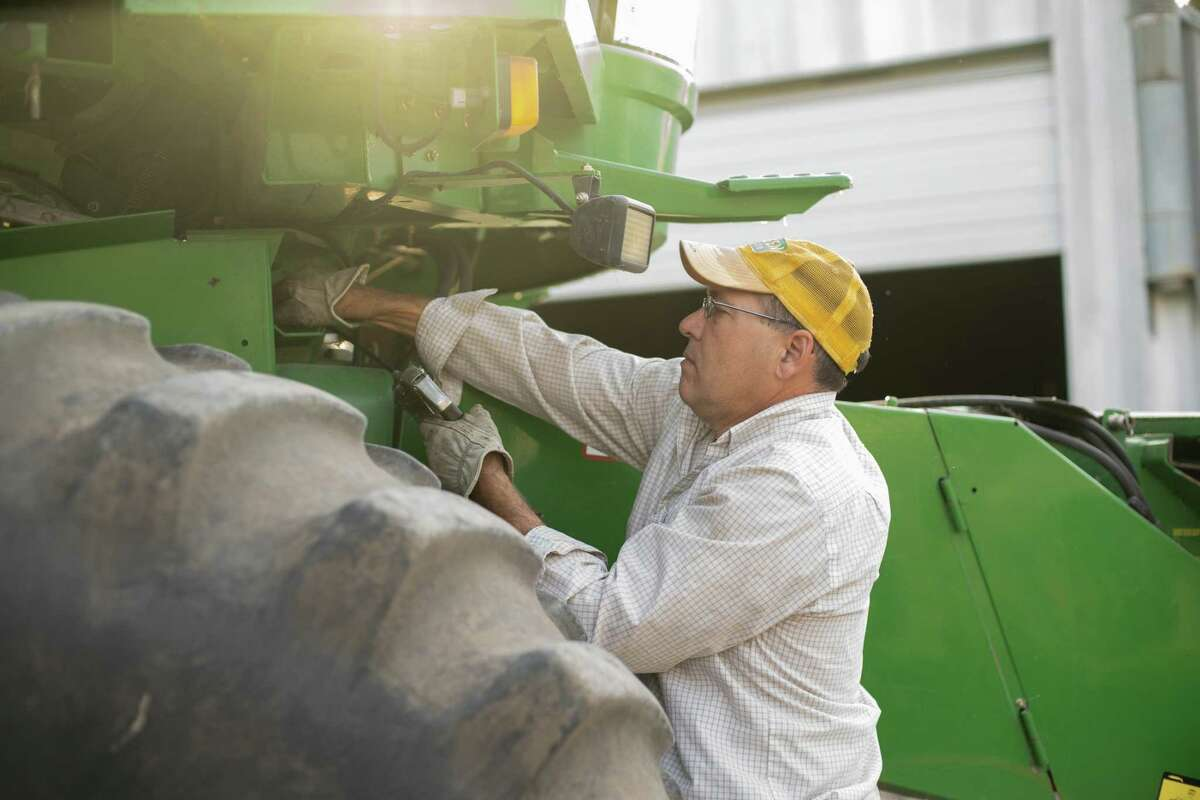 Alan Weisshaar, 55, a cattle, corn and bean farmer and Democrat, works on his combine on his family's farm in Creston, Iowa.