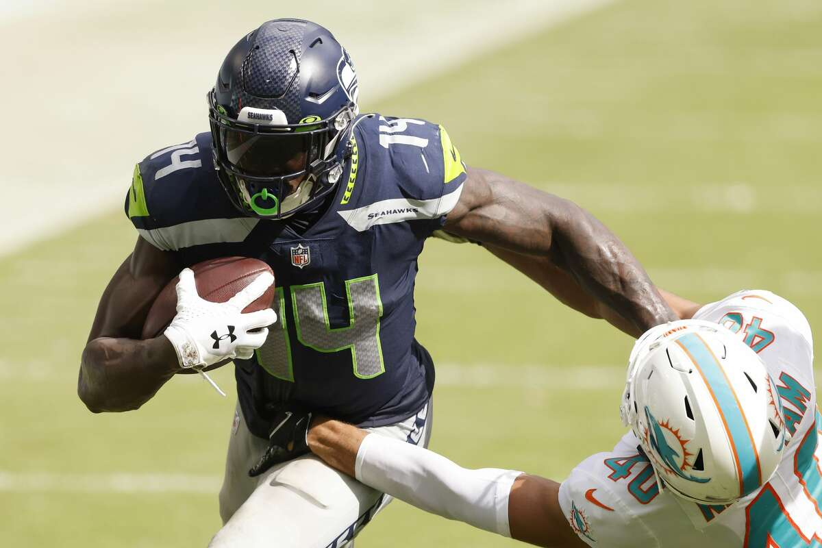 MIAMI GARDENS, FLORIDA - OCTOBER 04: DK Metcalf #14 of the Seattle Seahawks breaks a tackle from Nik Needham #40 of the Miami Dolphins during the fourth quarter at Hard Rock Stadium on October 04, 2020 in Miami Gardens, Florida. (Photo by Michael Reaves/Getty Images)