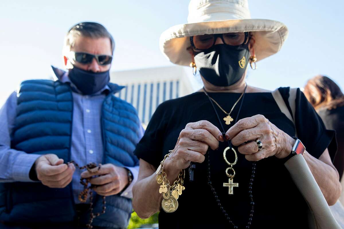 A woman who didn't give her name bows her head while reciting the Hail Mary prayer before San Francisco's Archbishop Salvatore Joseph Cordileone conducts an exorcism outside of Church of Saint Raphael in San Rafael, on the spot where a statue of St. Junipero Serra was toppled during a protest October 12.